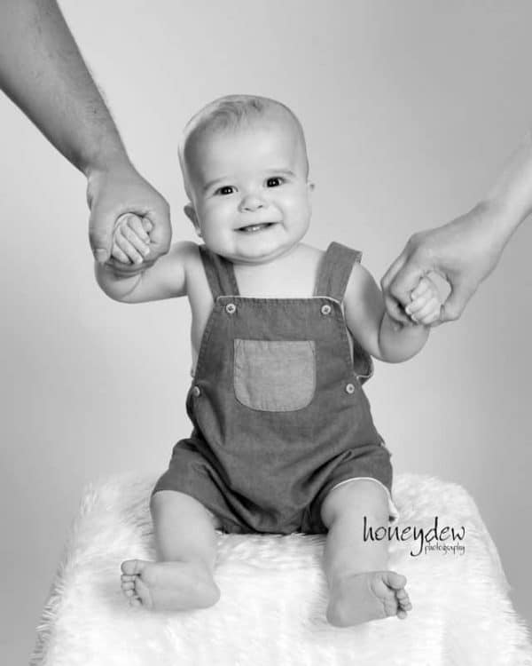 family photography Sydney baby smiling holding hands of parents