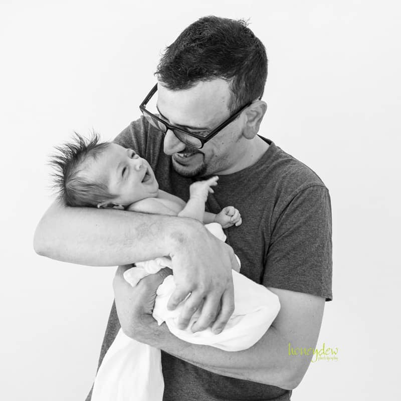 Dad with laughing newborn