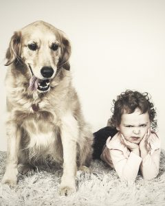 A grumpy looking child posing with her dog